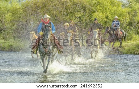 Cowboys galloping across river - stock photo