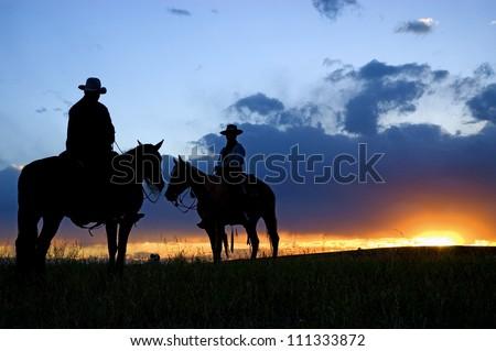 Cowboys on horseback as sun rises - stock photo