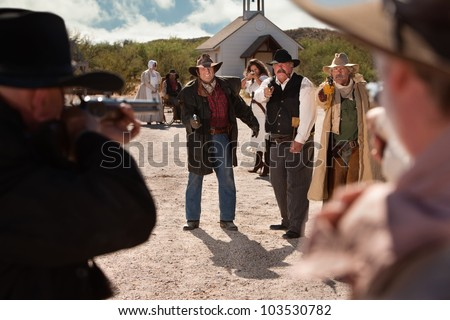 Cowboys pull out their weapons in an old west shoot out - stock photo