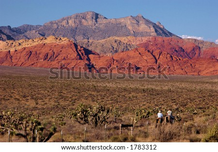 Cowboys riding into the sunset. Red Rock Canyon, Las Vegas, Nevada - stock photo
