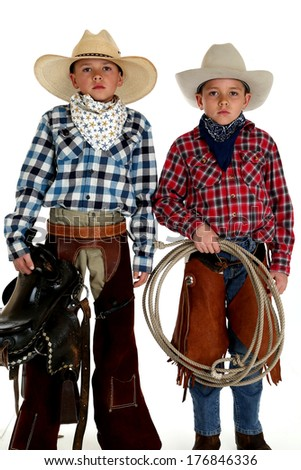 cowboys wearing hats holding saddle and rope