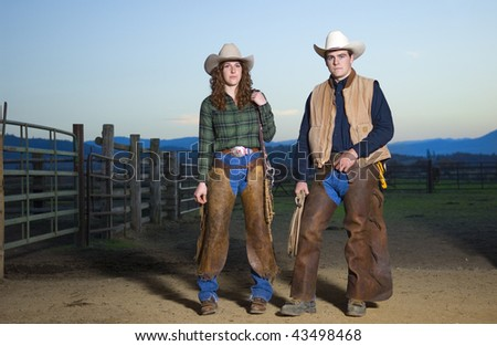 Cowgirl and cowboy couple against a sunset sky - stock photo