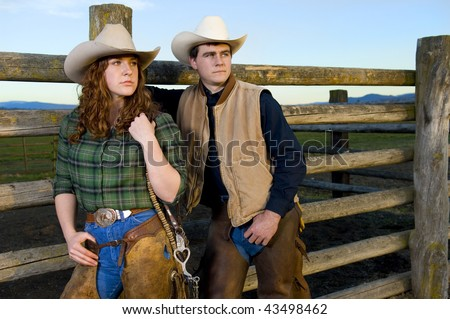 Cowgirl and cowboy leaning against a wood fence - stock photo