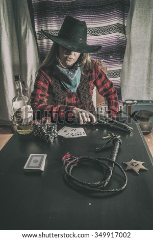 Cowgirl Gunslinger Poker Whip. Old west cowgirl gunslinger sitting at table player poker with peacemaker gun, edited in vintage film style. - stock photo