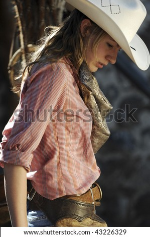 Cowgirl in a stone barn with her chaps and pink shirt