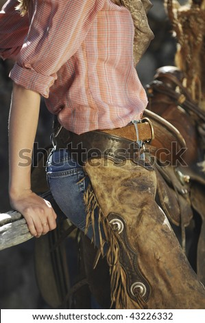 Cowgirl in a stone barn with her chaps and pink shirt - stock photo