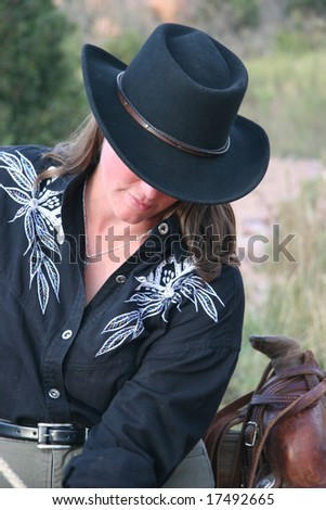 cowgirl in black hat and western shirt