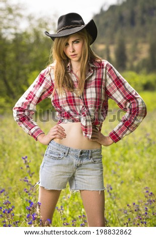 Cowgirl in red flannel shirt and denim shirts with cowboy for Country girl flannel shirts