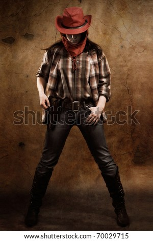 Cowgirl on a old wall background. - stock photo