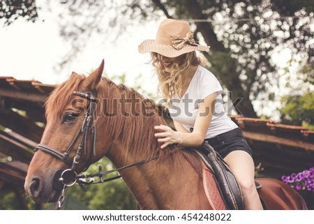 Cowgirl riding brown horse on such a beautiful day and feeling great