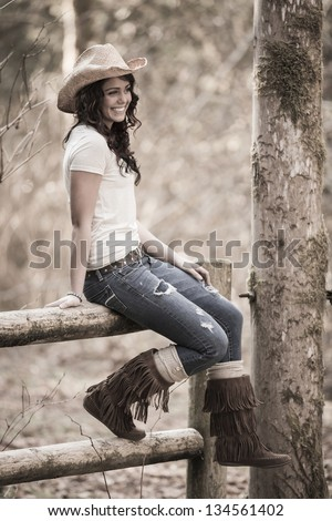 Cowgirl siting on the fence - stock photo