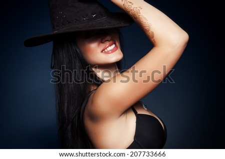 Cowgirl smiles in hat on blue background   - stock photo