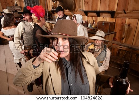 Cowgirl with bottle sipping whiskey from a shot glass - stock photo