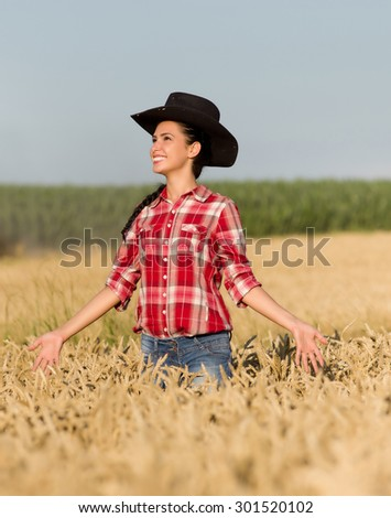 Cowgirl with plaid shirt and black hat walking in ripe wheat field in summer time - stock photo