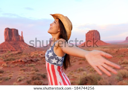 Cowgirl - woman happy and free in Monument Valley wearing cowboy hat with arms outstretched in freedom concept. Beautiful smiling multiracial young woman outdoors, Arizona Utah, USA. - stock photo