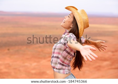 Cowgirl - woman happy and free on american prairie wearing cowboy hat with arms outstretched in freedom concept. Beautiful smiling multiracial Caucasian Asian young woman outdoors, Arizona Utah, USA. - stock photo