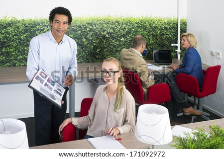 Coworkers discussing a project in an open office space - stock photo