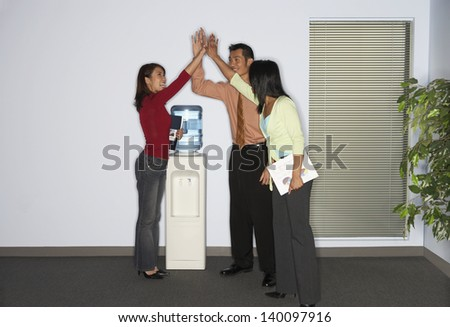 Coworkers exchanging a high five - stock photo