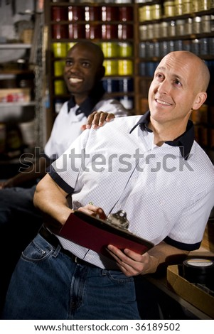 Coworkers in printing shop by shelves with inks