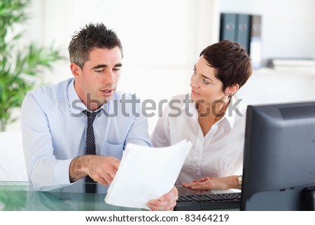Coworkers looking at a document in an office