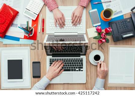 Coworkers sharing the same desk with customized workspace and working with a laptop, top view - stock photo