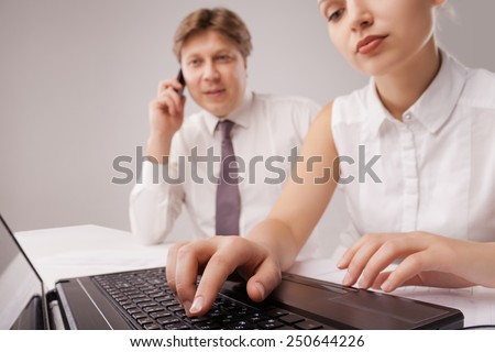 Coworkers working with a laptop and a cellphone in an office, the laptop is at the front - stock photo