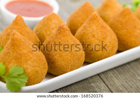 Coxinha de Galinha - Brazilian deep fried chicken snack, popular at local parties. Served with chili sauce.  - stock photo