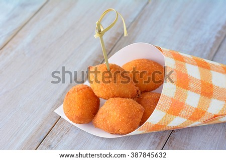 Coxinhas,  a popular food in Brazil consisting of chopped or shredded chicken meat, covered in dough battered and fried. Food background and texture - stock photo
