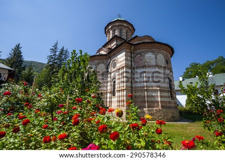 Cozia, Romania - Septemper 2, 2012: Cozia monastery church with red flowers on a sunny summer day, Romania - stock photo