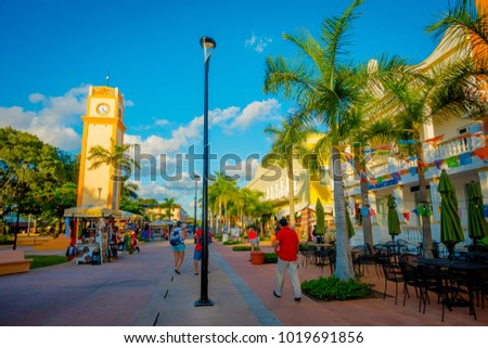 COZUMEL, MEXICO - NOVEMBER 09, 2017: Beautiful outdoor view of some tourists enjoying the city of Cozumel, surrounding of cars of locals in downtown