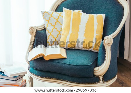 Cozy armchair with open book and decorative pillows. Interior and home decor concept - stock photo