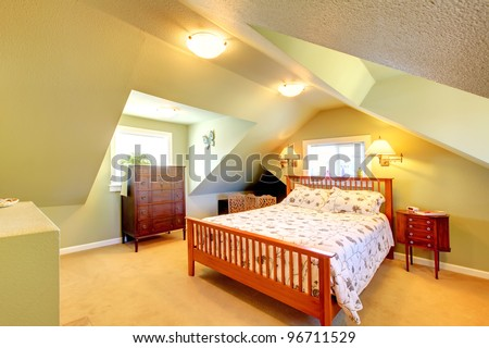 Cozy attic bedroom with green walls and large bed. - stock photo