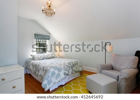 Cozy attic bedroom with white walls and yellow rug. - stock photo
