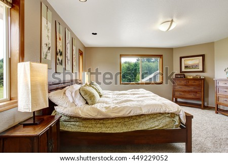 Cozy bathroom interior with double wooden bed, beige walls and carpet floor.