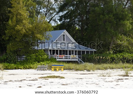 Cozy Beach House nestled in the shade of a tree grove on the beach - stock photo