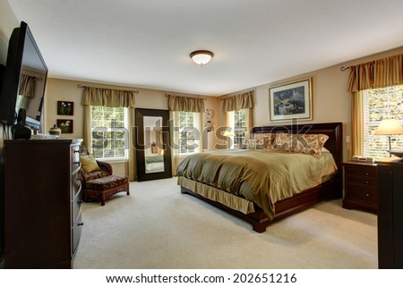 Cozy bedroom interior with carpet floor and wooden furniture set.  Room in olive olive colors - stock photo
