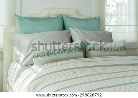 cozy bedroom interior with green pillows and reading lamp on bedside table - stock photo