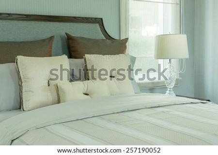 cozy bedroom interior with white pillows and reading lamp on bedside table - stock photo