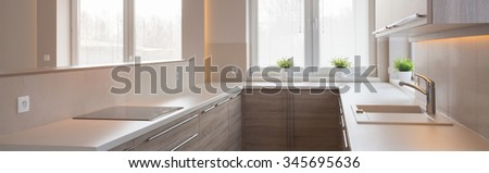 Cozy beige kitchen in traditional design - panorama - stock photo