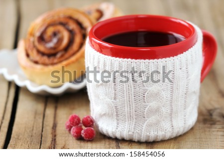 Cozy Christmas setting - a red mug of black coffee with aromatic homemade cinnamon rolls at the background on a rustic wooden kitchen table - stock photo