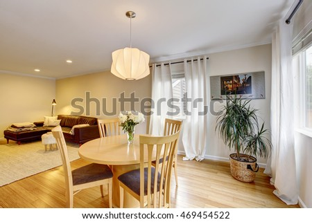 Cozy dining area with table set and curtains in creme tones. Open floor plan. Leather sofa at the background. Northwest, USA