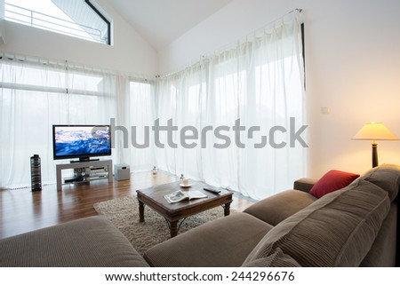 Cozy drawing room with comortable sofa and television - stock photo