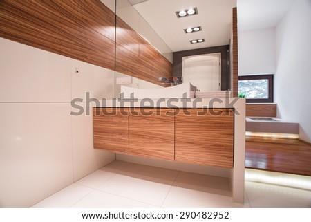 Cozy elegant white bathroom with wooden unit - stock photo