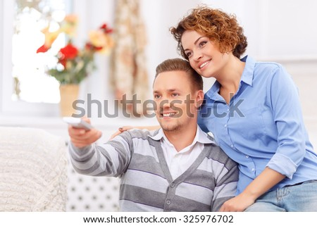 Cozy evening. Agreeable young cheerful couple bonding to each other and expressing love while watching TV - stock photo