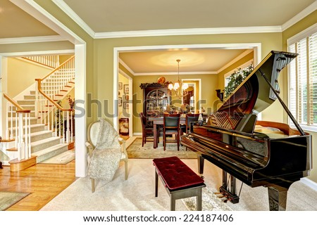 Cozy family room interior in luxury house. Room with grand piano. Dining area and white staircase - stock photo