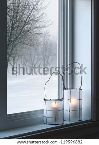 Cozy lanterns on a windowsill, with winter landscape seen through the window. - stock photo