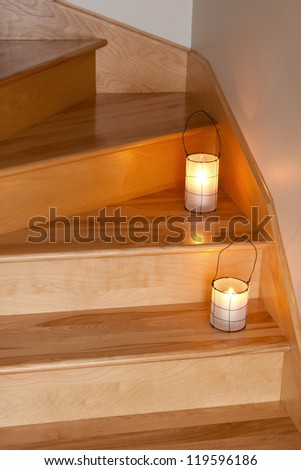 Cozy lanterns with candles decorating wooden staircase.