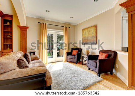 Cozy living room area with comfortable sofa, chairs and soft rug. View of glass door to the backyard