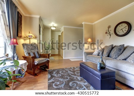 Cozy Living room design with nice decor, large beige sofa, clock and chair. - stock photo