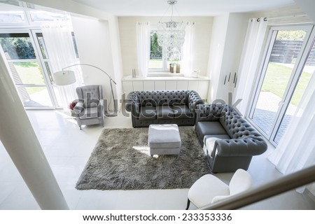 Cozy living room with garden view windows - stock photo